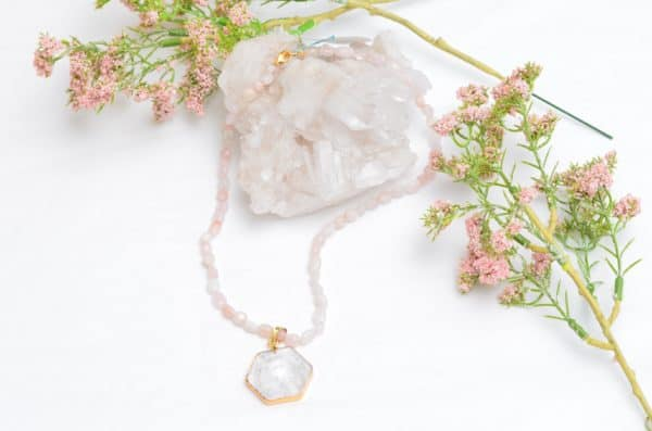 close up picture of a Pink Opal Necklace with Crystal Quartz Pendant on white background decorated with flowers by Kiskadee Design