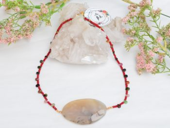 close up picture of an Agate Stone Necklace with Red Glass Beads and Tourmaline Drops on white background decorated with flowers by Kiskadee Design