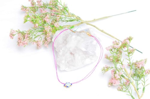 close up picture of an Enamel Charm Choker Necklace with Pink Silk Thread on white background decorated with flowers by Kiskadee Design