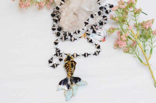close up picture of an Enamel Fish Pendant on a Long Sardonyx and Crystal Bead Necklace on white background decorated with flowers by Kiskadee Design