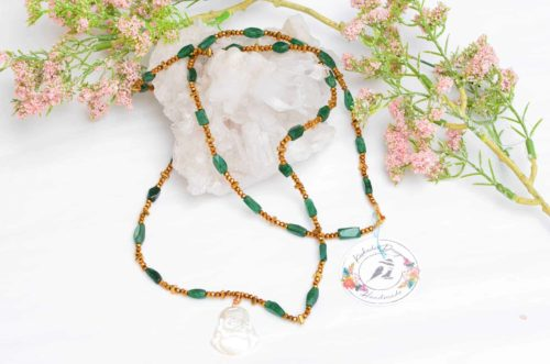 close up picture of a Long Raw Emerald Necklace with Mother of Pearl Buddha Pendant on white background decorated with flowers by Kiskadee Design