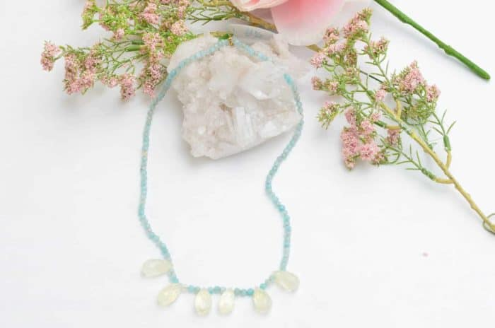 close up picture of a Smoky Quartz Necklace with Aquamarine Agate Beads on white background decorated with flowers by Kiskadee Design