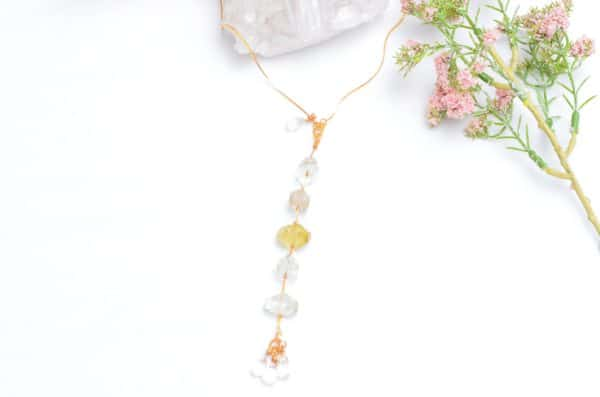 close up picture of a Raw Citrine Necklace with Delicate Gold-Filled Chain on white background decorated with flowers by Kiskadee Design