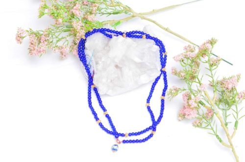 close up picture of a Blue Murano Bead Necklace with Enamel Charm and Gold-Filled Accent Beadson white background decorated with flowers by Kiskadee Design