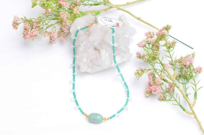 close up picture of a Amazonite Bead Necklace with Aquamarine Crystals and Faceted Crystal Drops on white background decorated with flowers by Kiskadee Design