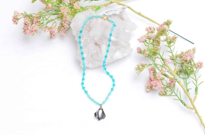 close up picture of a Turquoise Bead Necklace with Aquamarine Crystal Accents and Grey Crystal Pendant on white background decorated with flowers by Kiskadee Design