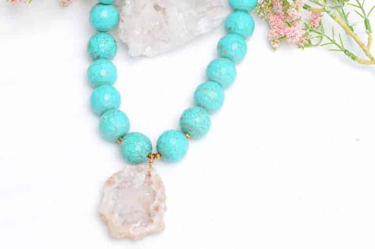 close up picture of a Turquoise Statement Necklace with Geode Pendant on white background decorated with flowers by Kiskadee Design
