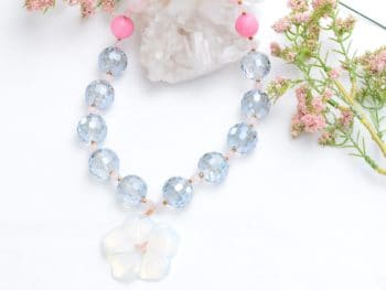 close up picture of an Opalite Carved Flower Pendant Necklace with Large Grey Crystal Beads on white background decorated with flowers by Kiskadee Design