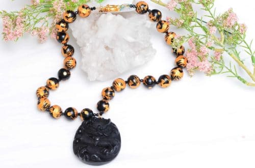close up picture of a Hand Painted Onyx Bead Necklace with Hand Carved Dragon Pendant on white background decorated with flowers by Kiskadee Design
