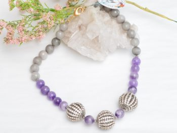 close up picture of an Amethyst Bead Necklace with Grey Agate and Crystal Accents on white background decorated with flowers by Kiskadee Design
