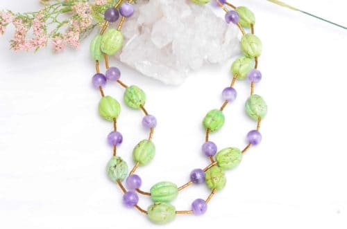 close up picture of a Gaspeite Necklace with Amethyst Beads on white background decorated with flowers by Kiskadee Design