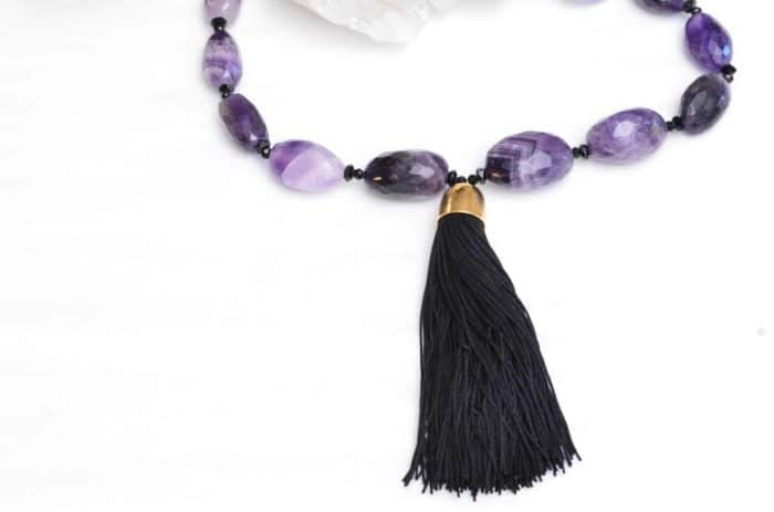 close up picture of a Tassel Pendant Necklace with Amethyst Beads on white background decorated with flowers by Kiskadee Design