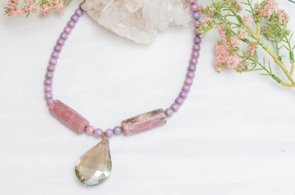 close up picture of a Lepidolite Necklace with Tear-drop Grey Crystal Pendant on white background decorated with flowers by Kiskadee Design