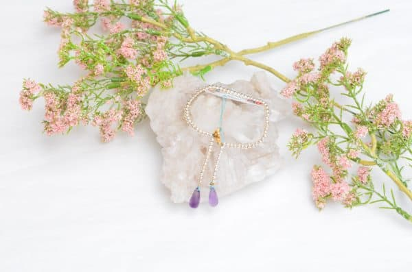 close up picture of an Amethyst Bracelet with Silver Beads on white background decorated with flowers by Kiskadee Design