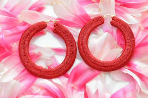 close up picture of a pair of Large Werregue Red Hoop Earrings on a pink petal backdrop