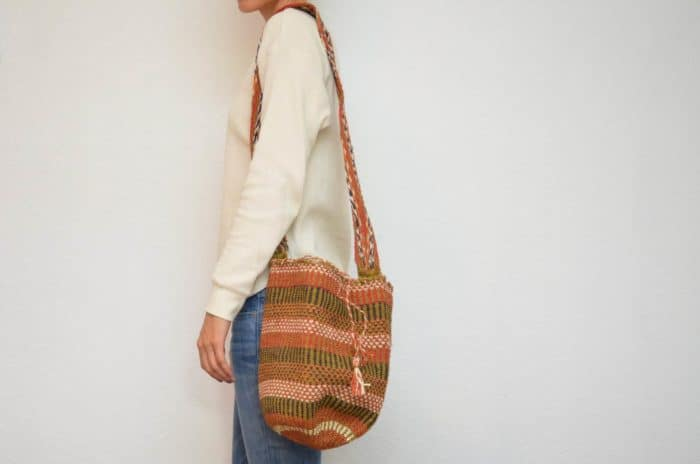 Kiskadee Design Image with Product being Used of a Los Haticos Pattern Handwoven Crossbody Bag by Women from the Kankuamo Indigenous Tribe in the Sierra Nevada de Santa Marta - Colombia
