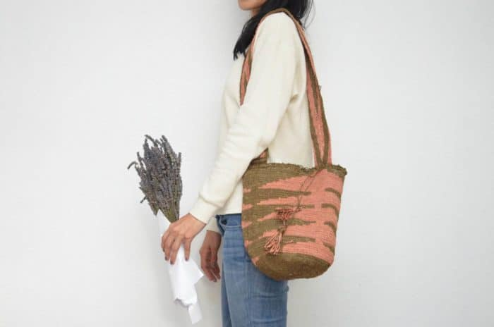 Kiskadee Design Image with Product being Used of a Green and Pink Pattern Boho Crossbody Bag by Women from the Kankuamo Indigenous Tribe in the Sierra Nevada de Santa Marta - Colombia