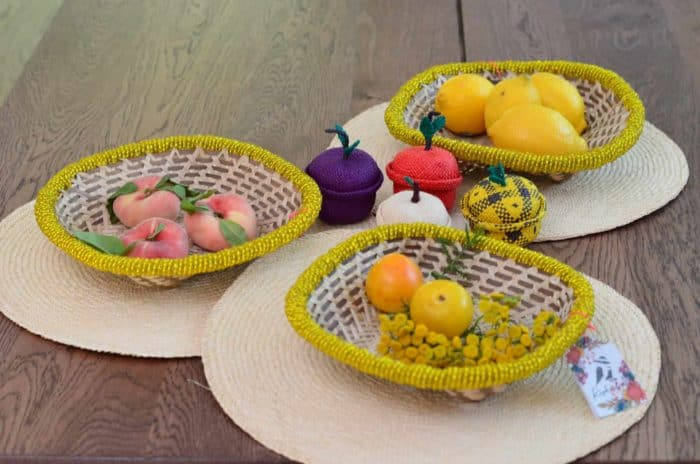 Kiskadee Design Image with Product being Used of a Pineapple, Grape and Apple-Shaped Tiny Woven Baskets by the artisans in Sandona Narino sitting next to small bread baskets with yellow beaded border
