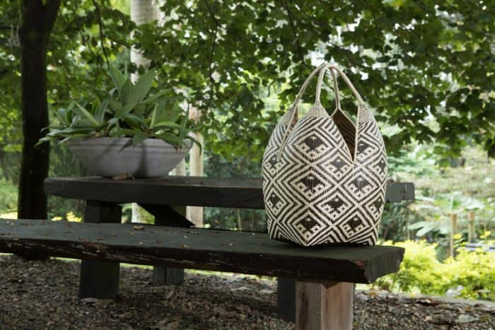 Kiskadee Design Image with Product being Used 2 of a Black and White Fish Pattern 27 inches High 4 Tetas Basket handwoven by artisans in Colombia
