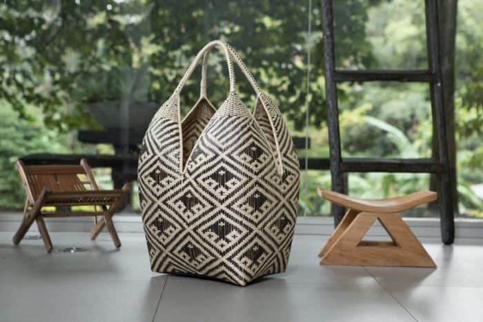Kiskadee Design Image with Product being Used of a Black and White Fish Pattern 27 inches High 4 Tetas Basket handwoven by artisans in Colombia