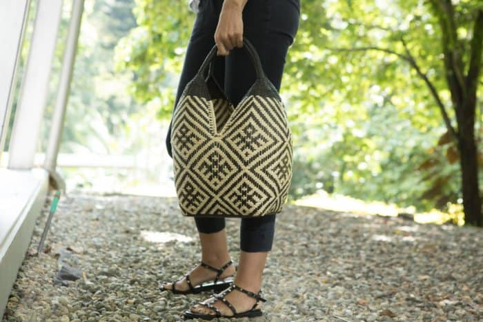 Kiskadee Design Image with Product being Used as a handbag of a Beige and Black Spider Pattern with Black Handles 20 inches High Cuatro Tetas Basket handwoven in Colombia