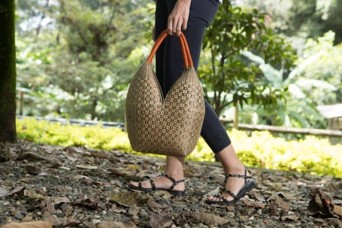 Kiskadee Design Image with Product being Used as a handbag of a Tan and Light Green Button Pattern with Orange Handles 20 inches High Cuatro Tetas Basket handmade in Colombia