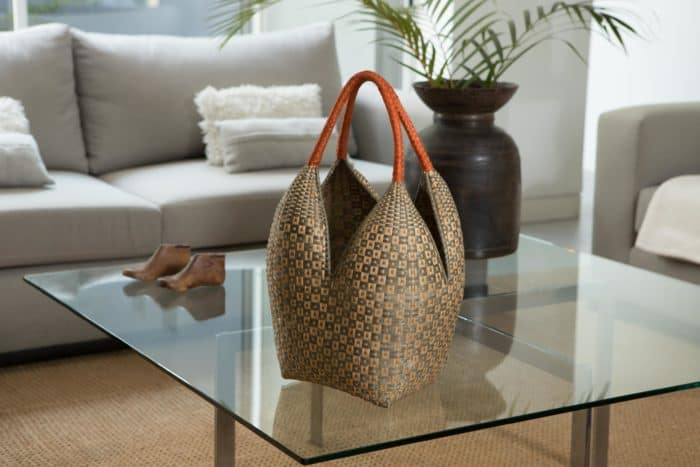 Kiskadee Design Image with Product being Used as home decor of a Tan and Light Green Button Pattern with Orange Handles 20 inches High Cuatro Tetas Basket handmade in Colombia
