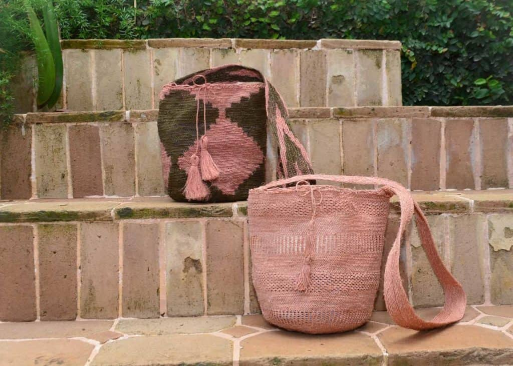 Kiskadee Design Catalogue Image of two natural fique mochilas, made by the Kankuamo indigenous tribe handmadein Colombia with natural fique fibers