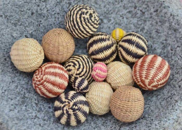 Kiskadee Design Catalogue Image of a Beautiful accessories made by women artisans in Sandona Narino Woven decorative accents handmade woven balls made from Iraca fibers.