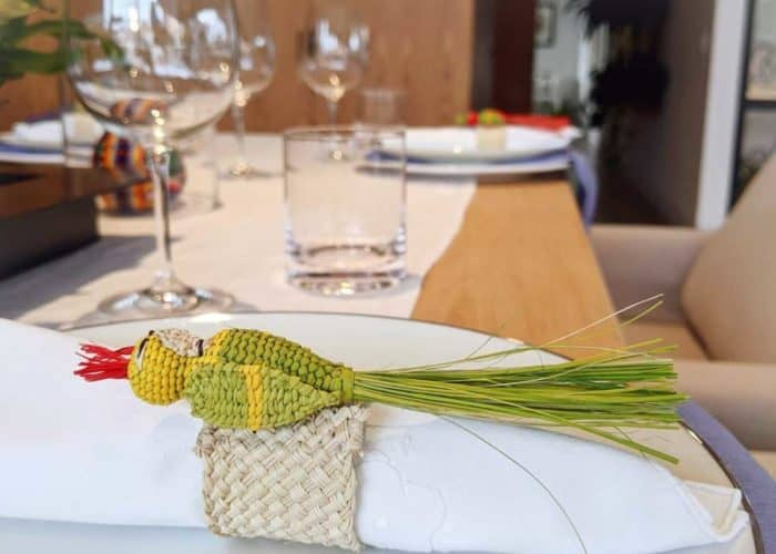 Kiskadee Design Image with Product being Used 2 of a Beautiful table accents. Made in Sandona Narino Natural fiber bird napkin rings handmadein Colombia with natural iraca fibers