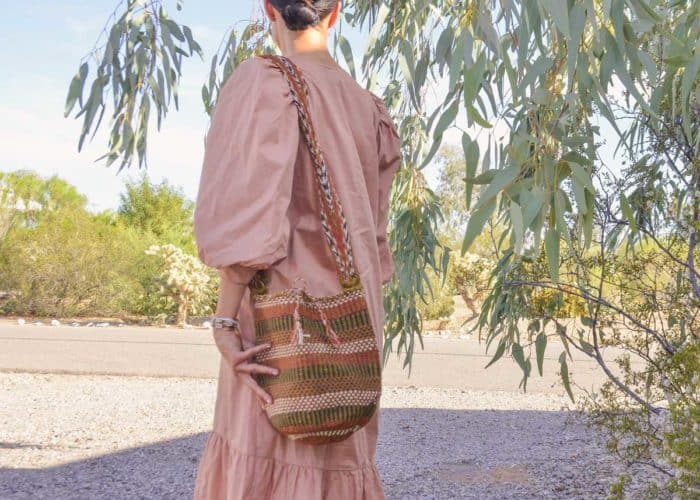 Kiskadee Design Image with Product being Used of a Made by women from the Kankuamo tribe in the Sierra Nevada de Santa Marta - Colombia Handwoven Kankuamo Fique Mochila - LOS HATICOS handmade woven shoulder bag in colorful pattern